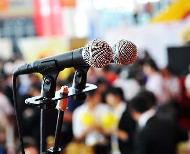 speakers_bureau_two_microphones_in_front_of_crowd